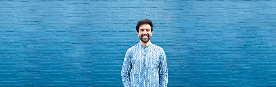 Picture of Zohran in a blue shirt smiling posed on a bright blue wall